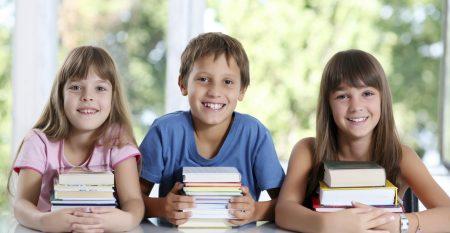 Happy schoolchildren with many books.